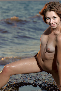 Oda bares her slender, wet body as she poses playfuly poses on the beach.