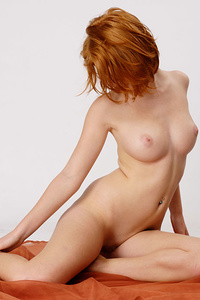 Redhead Clelia displays her creamy, white body and pink pussy in front of the camera.