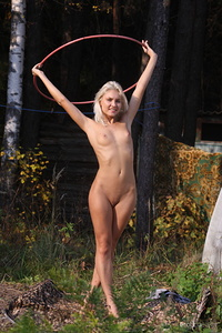 Kristy playfully poses with her naked body in the outdoors