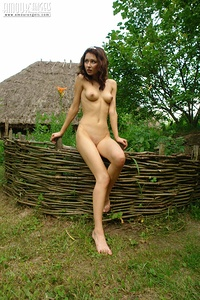 Adorable naked angel exposing her provocative beauty and delicious natural body against the background of an obscure country