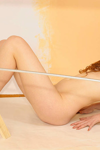 Tremendous charming coquette has taken off all her clothes to paint the walls in her room in orange colour.