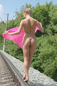 Attractive busty angel is standing on the railways fully nude and it is so hot for her that she pours upon herself from the bottle.