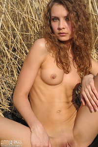 Her blonde curly hair matches wit the background as she is stretching her slender body with her boobs hard as  a rock.