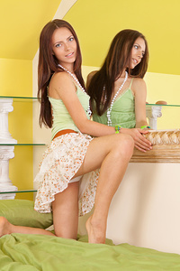 Adorable dark haired teen chick spreading legs and showing her alluring pussy on the bed.
