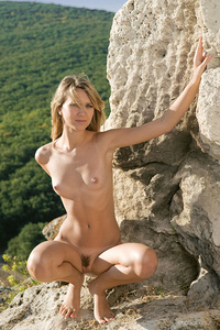 Viki D flaunts her slender body and trimmed pussy by the cave.