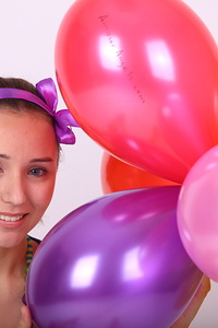 A very attractive teen girl gets playful with balloons and shows off her naked amenities.