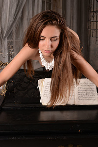 Flawless teen babe showing off her amazing curves on a piano with an artistic form that expresses deep beauty and sexiness.