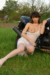 Thrilling nude angel is sitting on a big black motorbike in white stockings and caresses her sweet boobies.