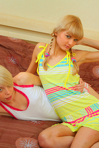 Cute blonde girls caress each other on the bed and get real pleasure.