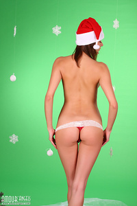 Perfect brunette teen in Santas Hat and dotted red pants strips and seduces us with her fantastic forms.