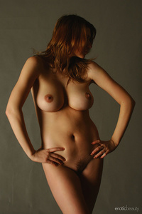 Maria D poses playfully in front of the camera, displaying her large cuppable breasts.
