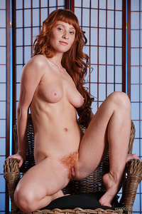 Redhead Oxavia flaunts her sexy body with beautiful breasts and hairy pussy as she   poses on the chair.